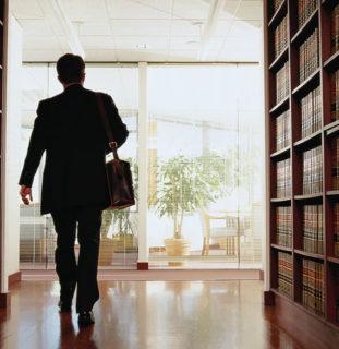 Un hombre camina por una biblioteca