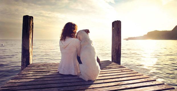 Mujer con su perro frente al mar