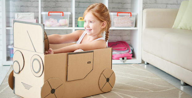 Niña jugando con una caja de cartón