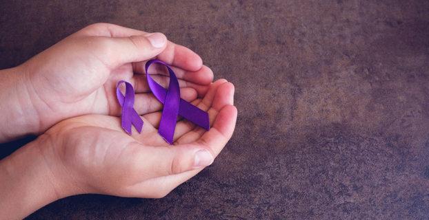 Manos sostienen lazos violeta