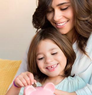 Madre e hija meten una moneda en una hucha