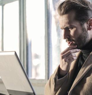 Hombre sentado frente a un portátil